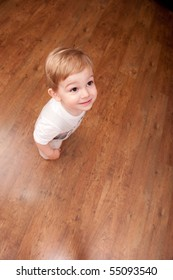Little boy is standing on brown floor. Place for text.
