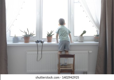 The little boy is standing on the children's chair and looking out the window