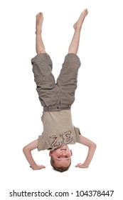 little boy standing on hands in front of a white background