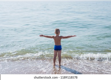 Little boy is standing on the seashore and holding hands up like flying.