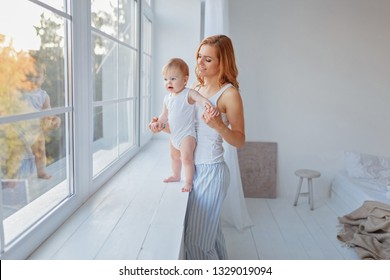 A little boy is standing on the window sill near the window, and his mother is holding his hands / copy space.