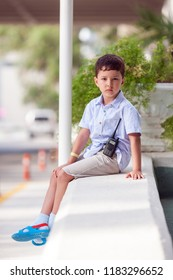 A little boy is standing outside with a walkie-talkie