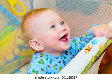 little boy standing in the playpen for babies