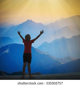 Little boy standing with raised hands above the mountain valley in a light of sunrise.