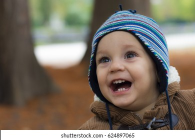 Little boy standing and smiling in autumn park