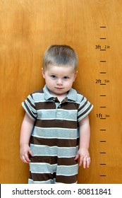 Little boy stands against a wooden door.  Besides him is his growth chart.  Feet and inches have been marked as he continues to grow taller and taller.