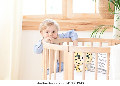 little boy stands alone beside a cot in the nursery. Lonely baby is in kindergarten near the crib. Loneliness. Eco-friendly children's room decor in the Scandinavian style.  The boy is at home.
