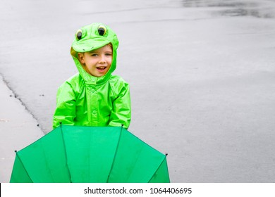 A little boy stands on a street in a frog raincoat and holding a green umbrella in front of him on a rainy day.  There is a lot of copy space.  The boy is smiling and has Ptosis of the eye.