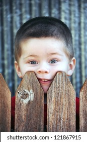 Little boy stares over his backyard fence.  His face is pressed against the wooden slats and his mouth is pushed crooked.