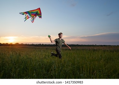 A little boy starts a kite at sunset in a field and runs with it.