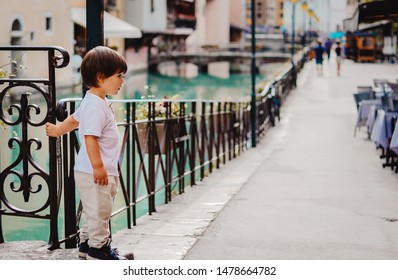 Little boy staying at street near the bridge of Thiou River in Annecy, France. Child in the city. Little tourist, summer lifestyle. Discovering Europe, traveling with kid.