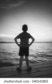 Little boy stays on a pier and enjoy sunset on a sea. Black and white.