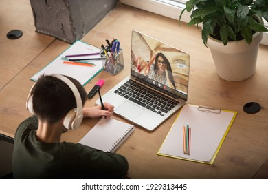 Little boy studying by group video call, use video conference with teacher, listening to online course. Using stationery, notebook. Easy, comfortable usage concept, education, online, childhood.