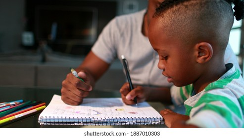 Little boy studying at home doing homework with father help