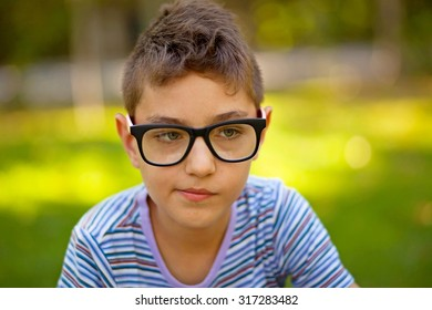 A little boy with stylish glasses sitting in a green park in summertime.