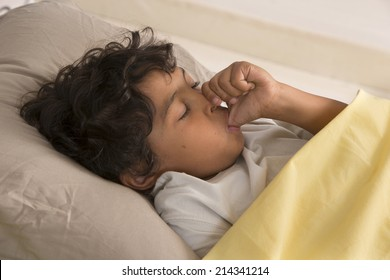 little boy sucking his thumb at night