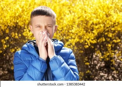 Little boy suffering from seasonal allergy outdoors, space for text