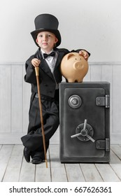 Little boy in a suit of the banker at the safe with a coin box