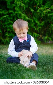 little boy in a suit playing in the park with a rabbit.