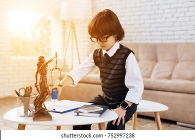 A little boy in a suit presents himself as a lawyer. The dark-haired boy plays a rich man. The boy puts a seal in the documents. On the table is a statuette of the femida and stationery.