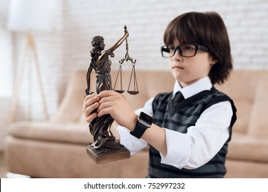 A little boy in a suit and tie is holding a figurine of a femida. The dark-haired boy in glasses looks at the statuette of justice. A little future lawyer.