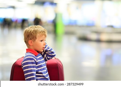 little boy with suitcase waiting in the airport, kids travel