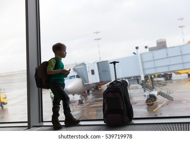 little boy with suitcase waiting in the airport