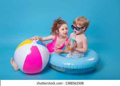 Little boy in sunglasses with inflatable ring toy and girl with big inflatable ball on blue background