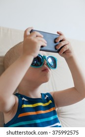 Little boy with sunglasses playing a game on smart phone