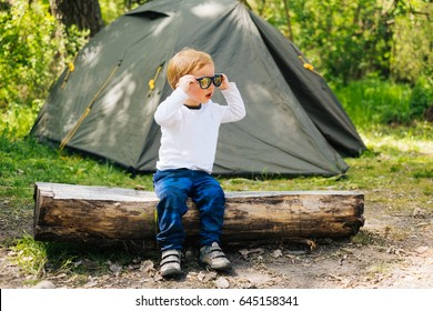 Little boy in sunglasses sit on wooden bench near camping tent on summer holidays outdoors. Child travel on nature. Traveler kid leisure activity.