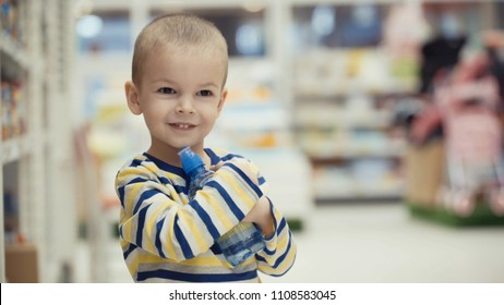 Little boy in the supermarket choose a bottle of mineral water