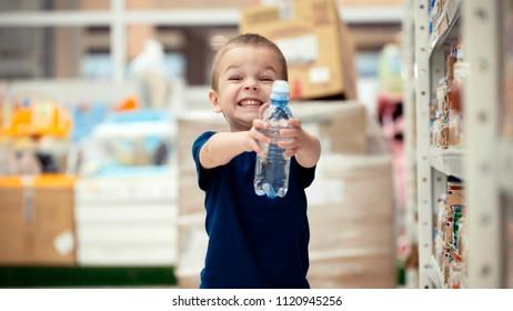 Little boy in the supermarket choose a bottle of mineral water