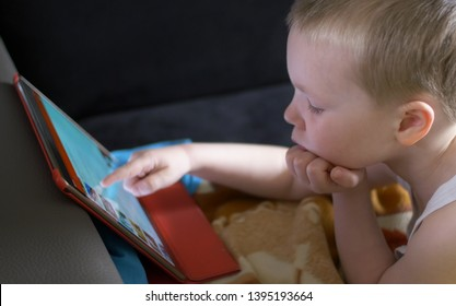 little boy surfing internet on tablet while laying on sofa at home. children online concept, safety online internet for child.