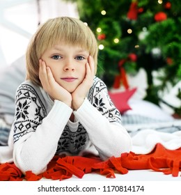 A little boy in a sweater near the Christmas tree. Square. The concept of Christmas and New Year.