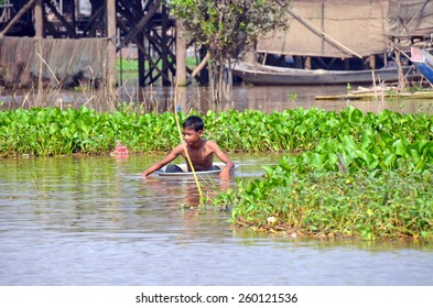 Little boy swimming in aluminum basin in the muddy water of the river Tonle Sap ,Siem Reap, Cambodia ,December 11, 2012