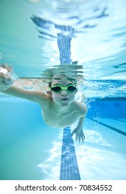 little boy swimming freestyle, seen from underwater