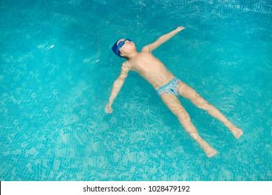 Little boy swimming in the pool , having fun in swimming pool.