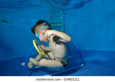 Little boy swims and plays sports underwater in the pool with hoops and rings. Close-up. Shooting underwater. Landscape orientation