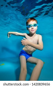A little boy swims and plays underwater in the pool with his arms apart and looks at the camera. Dancing underwater. Portrait. Underwater photography. Vertical orientation of the image