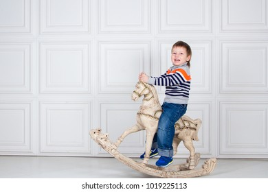 little boy swinging on wooden horse. funny three-year-old boy in jeans and sweater on white background. Carefree childhood, baby smile