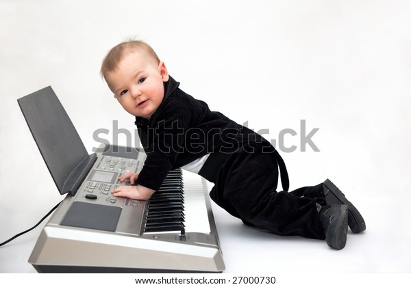 little boy in tailcoat playing piano