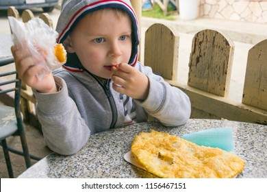 The little boy takes a bite with a cheburek.