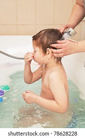 Little boy taking bath, hands of his mother washing his head