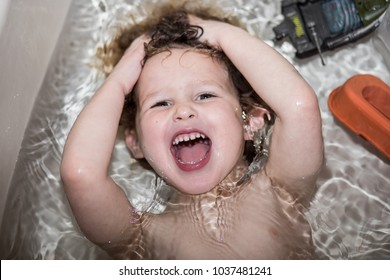 A little boy is taking a bath with his toys in the bathtub. His head is under the water and he is laughing and smiling for the camera. The child is having a great time in the bathtub