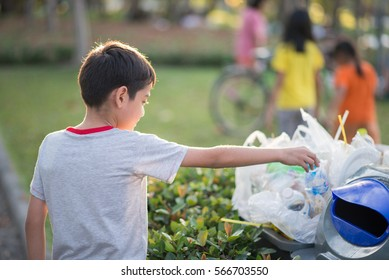 Little boy taking garbage in to the bin in the park