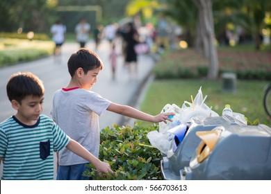 Little boy taking garbage in to the bin in the park