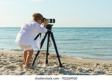 Little boy taking pictures of the sea