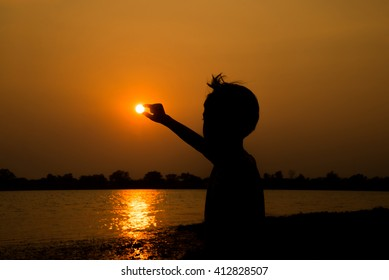 little boy taking sun by finger  silhouette