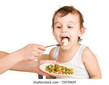 Little boy tasting vegetable salad