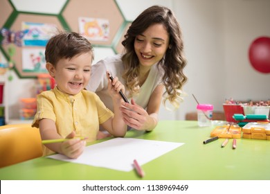 Little boy and teacher draw on paper with color pencils